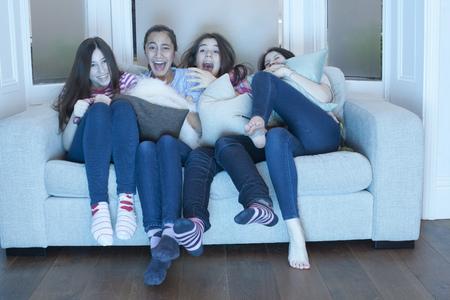 shocks: teenage girls watching tv on sofa LANG_EVOIMAGES