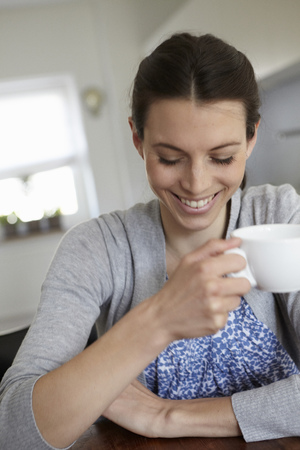 fulfill: Smiling woman drinking cup of coffee