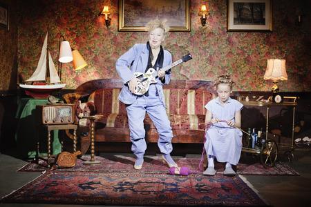 musically: Older woman playing guitar as girl knits