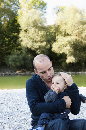 cries: Father holding crying baby by creek
