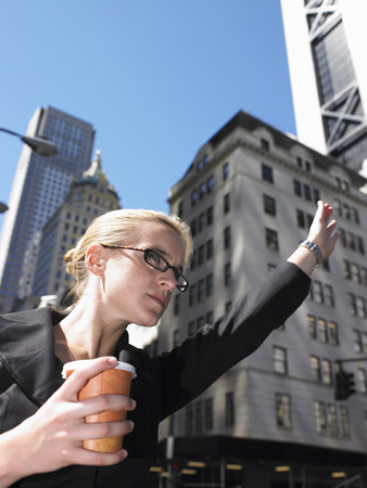 tardiness: Business woman calling a taxi LANG_EVOIMAGES