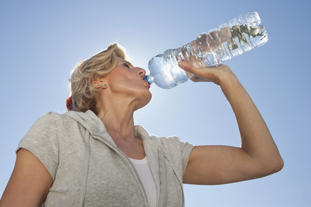 Mature woman drinking water from bottle