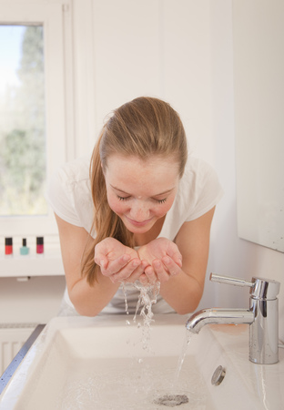 sinks: Teenage girl washing face in bathroom