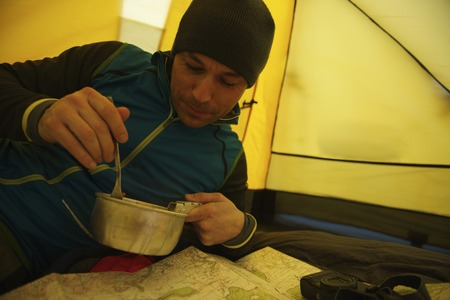 strategize: Man eating in camping tent