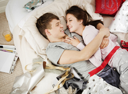 snuggle: Couple in bed laughing,with presents