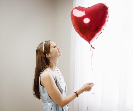 Vrouw die hart gevormde ballon bekijkt