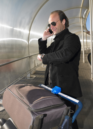tardy: Man at the airport on the phone LANG_EVOIMAGES