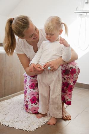 arrodillarse: Madre vestir a su hija en el baño