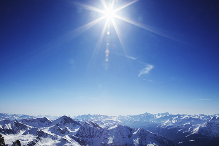 Sun over snow covered mountains