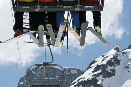 Skiers riding chair lift over mountains