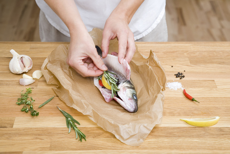 Preparing fish with herbs,spices,lemon