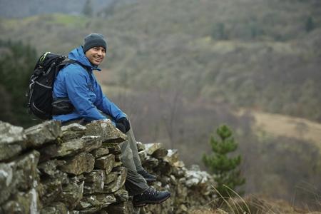 Hiking man sitting on stone wall