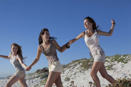 low spirited: Three girls running down hill LANG_EVOIMAGES