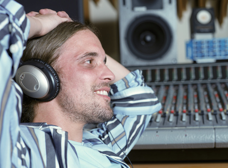 musically: Man at control panel in recording studio