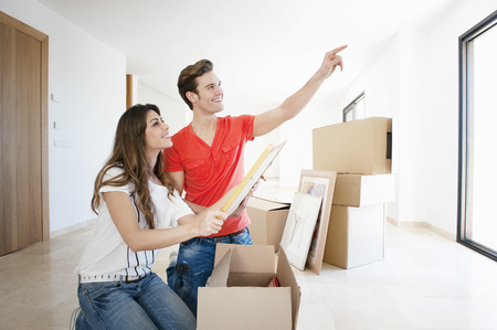 Couple unpacking box in new home LANG_EVOIMAGES