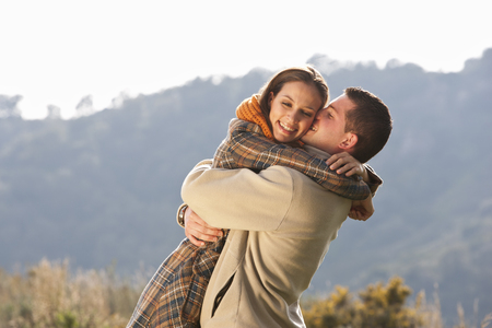 smooching: Young couple embracing in rural scene