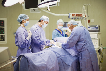 operation gown: Doctor and nurses performing operation