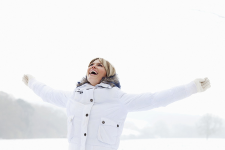 enthusiastically: A woman arms outstretched in the snow