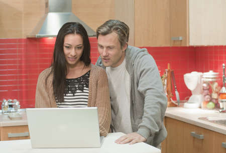 shared sharing: Couple in kitchen with laptop computer
