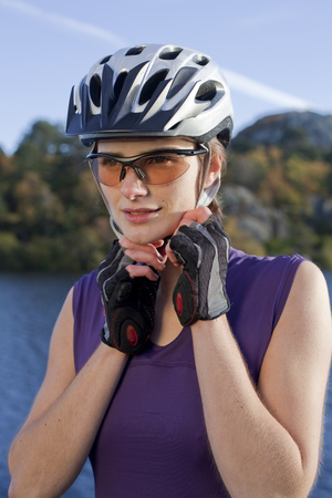 fastened: woman putting on a cycling helmut