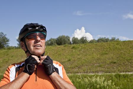 adventuring: Older man fastening bike helmet
