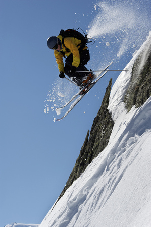 Skier jumping over steep mountain face