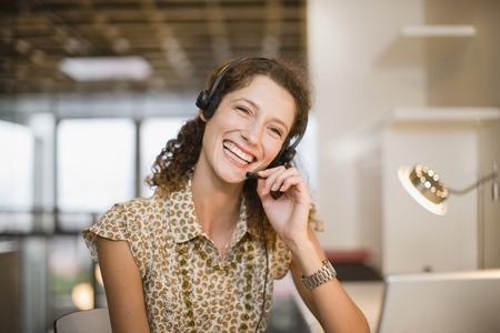 handsfree telephones: Smiling woman wearing headset LANG_EVOIMAGES