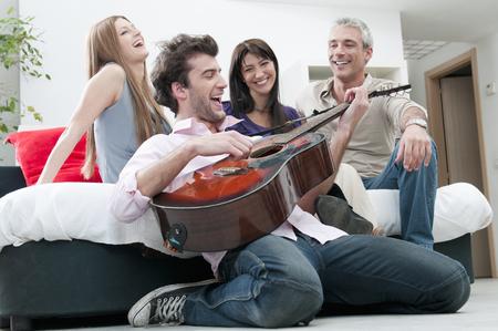 Joyful friends singing and play guitar