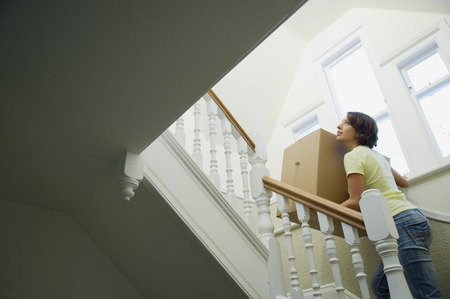 ascends: Woman carrying cardboard box upstairs