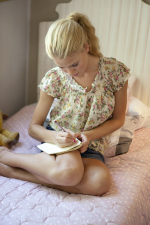 Girl writing diary LANG_EVOIMAGES