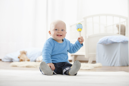 vibrations: Baby boy playing with rattle