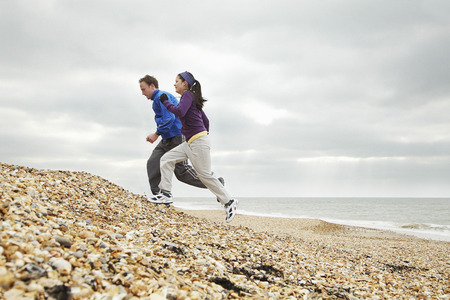 stoney: Couple exercising on stoney beach LANG_EVOIMAGES