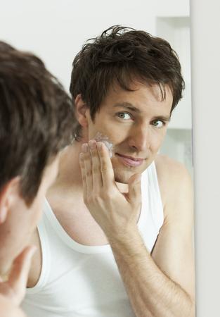 applied: Man moisturizing face in bathroom LANG_EVOIMAGES