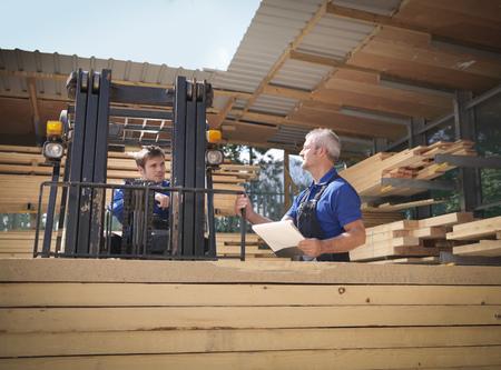 stockmarket: Worker carrying planks on forklift