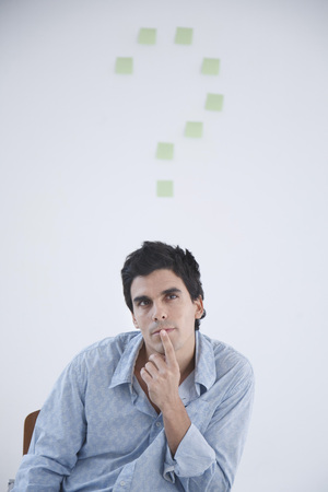 interrogations: Man thinking with post-it note question makr behind him