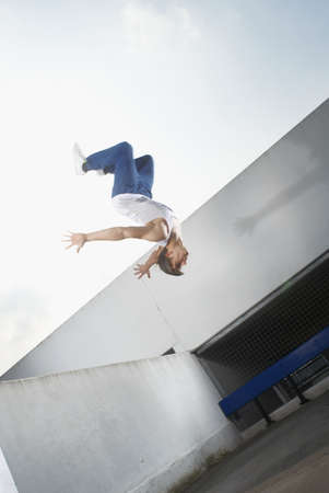 jeopardizing: Man jumping on urban rooftop LANG_EVOIMAGES