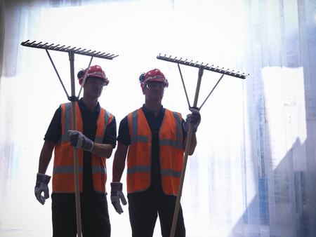 advancing: Workers holding rakes