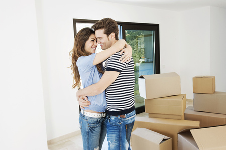 milestones: Couple hugging in new home LANG_EVOIMAGES