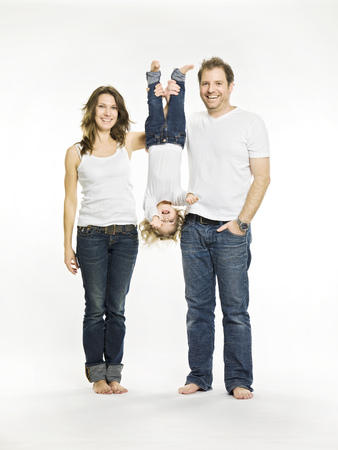 Parents holding daughter upside down LANG_EVOIMAGES