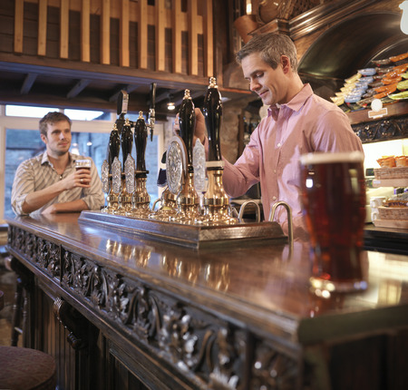 Landlord and customer in English pub LANG_EVOIMAGES