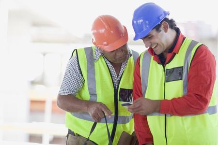 reconocimientos: Trabajadores de la construcción escribiendo un sms LANG_EVOIMAGES