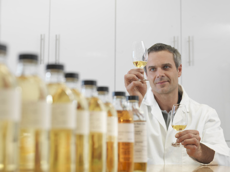 analyses: Scientist tasting whisky in plant