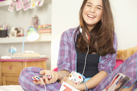 pubescent: teenage girl listening to music in pajamas