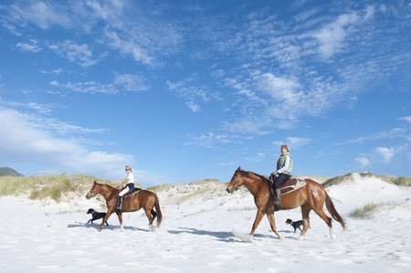 2 people riding horses on the beach LANG_EVOIMAGES