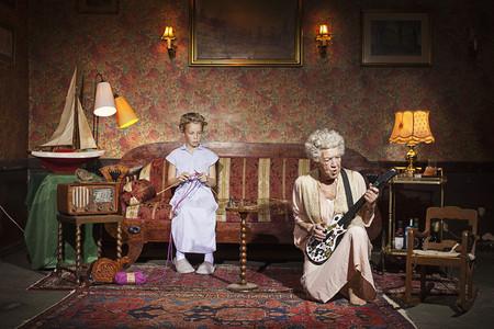 Older woman playing guitar as girl knits