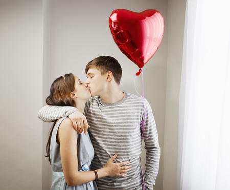 Couple kissing,holding heart balloon LANG_EVOIMAGES