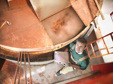 the brewer: Worker at copper tank in brewery