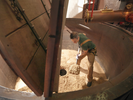 the brewer: Worker shovelling used hops in brewery LANG_EVOIMAGES