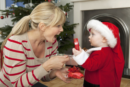 knelt: A mother gives her son a Christmas gift