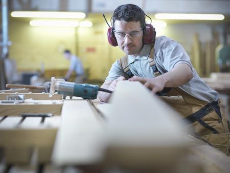 koncentrovaný: Pracovník na dřevo v dílně LANG_EVOIMAGES
